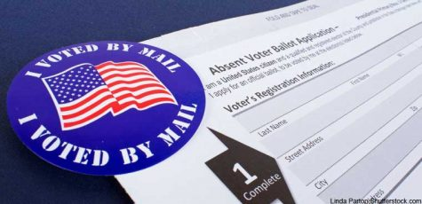 An image of a blue I voted by mail sticker, with an American flag displayed over it. Beneath the sticker is a blank white voting ballot.